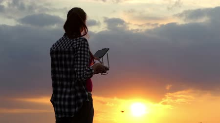 unmanned aircraft : Slim woman operates a panel to control a drone at sunset Stock Footage