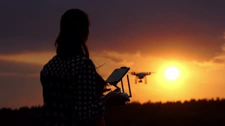 sky only : Nice woman works with a panel to control a drone at sunset