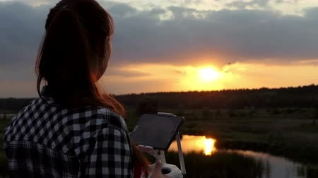 só as mulheres jovens : Fine woman works with a panel to control a drone at sunset