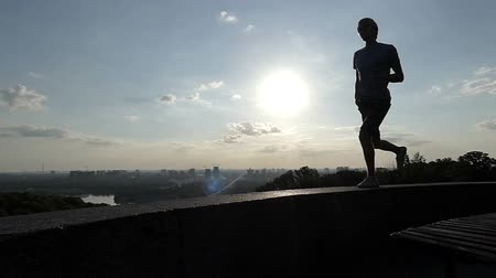 going round : Young man runs on a curb of an observation deck in Kyiv in slo-mo Stock Footage
