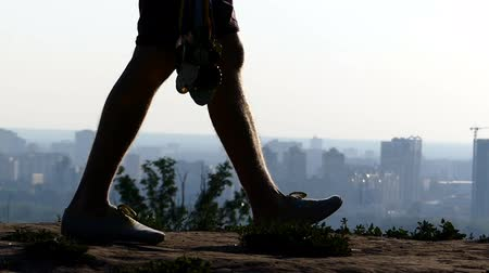 observation deck : Young man goes with medals in a hand and a cityscape in slo-mo Stock Footage