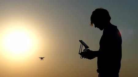 летчик : Smart man directs the flight of a drone at a golden sunset in slo-mo