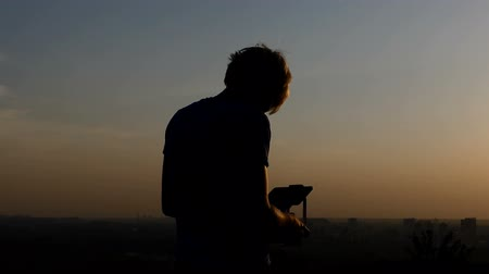 nádech : Young man controls the flight of a drone at a nice sunset