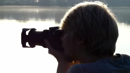splendid : Blond man shoots a forest lake at a splendid sunset in summer Stock Footage
