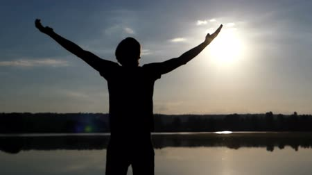 Çapraz kollar : Blond man raises hands happily on a lake bank at sunset Stok Video