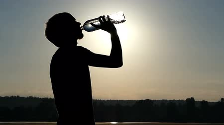 napoje : Stylish man drinks water from a plastic bottle at sunset in slo-mo