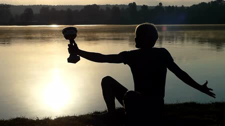 award : Blond man sits on a lake bank looking at a winner bowl in slo-mo