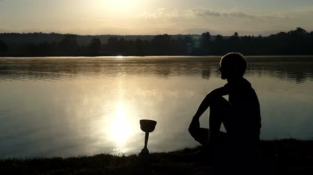 fabuloso : Brave man looks at his champion bowl at a lake in slo-mo