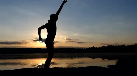 handstand : Young man dances disco on a lake bank at sunset in slo-mo