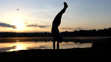 handstand : Young man stands on his hands and walks at sunset