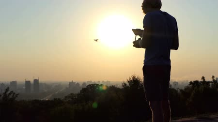 стабильность : A cameraman uses his flying quadracopter at sunset in slo-mo Стоковые видеозаписи