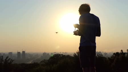intruder : Smart cameraman uses a flying quadracopter at sunset in slo-mo Stock Footage