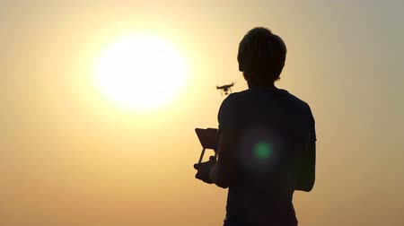 stable fly : Blond cameraman uses a flying quadracopter at sunset in slo-mo