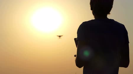 летчик : Happy man uses a new flying quadracopter at sunset in slo-mo
