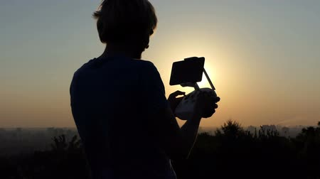 hélice : Excited man controls a brand new drone at sunset in slo-mo Vídeos