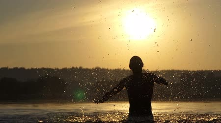plavec : Happy man raises the lake water to entertain at sunset in slo-mo Dostupné videozáznamy