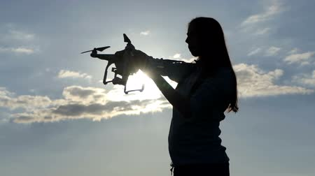 vnější : Young woman inserts a battery in a quadracopter at sunset in slo-mo