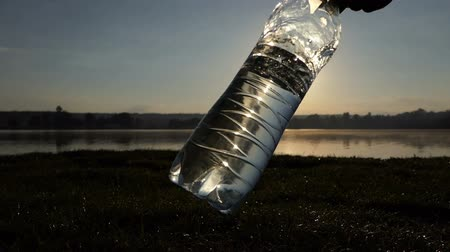 hydratace : Plastic bottle with water is swayed on a lake bank at sunset in slo-mo