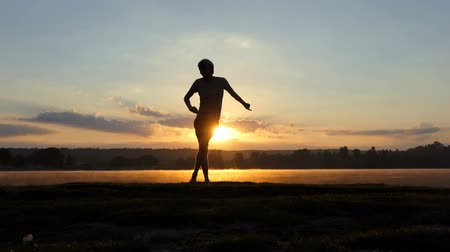 ballroom : Stylish man dances free style on a lake bank at sunset in slo-mo Stock Footage