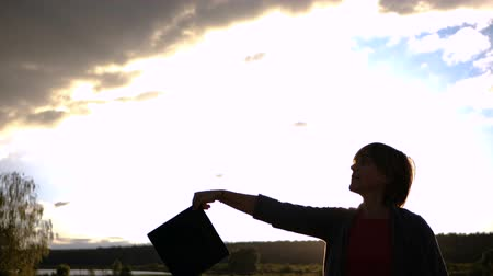 master's degree : Middle aged woman student throwing her hat in slow motion. Stock Footage
