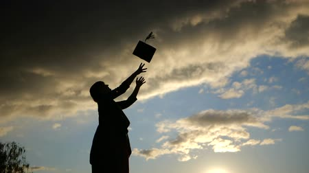 mezun : Silhouette of Woman student throwing her hat in slow motion at sunset. Stok Video