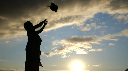 graduação : Woman student throwing her hat in slow motion at sunset.