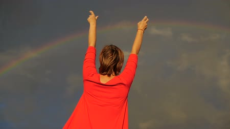hippi : Woman that shows her thumbs and sign peace into the sky during rainbow