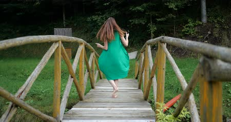 ormanda yaşayan : Emotional dance of the young girl in green dress on the wooden bridge. Stok Video