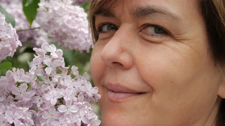tur : The face of a beautiful smiling woman among the lilac close up