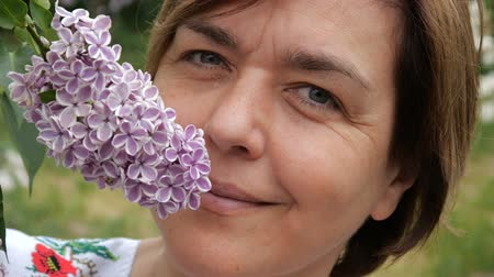 фиолетовый : Beautiful woman smiling near lilac bud close up