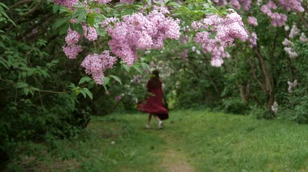 go away : The woman goes away in the park with blooming lilac bushes