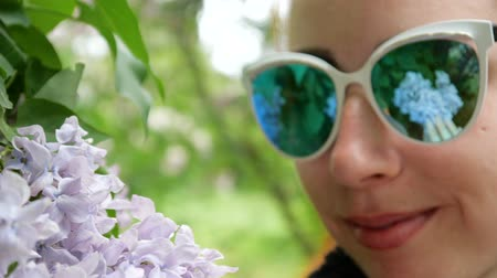 leylak : Lilac close up is reflected in the sunglasses on the face of a young girl