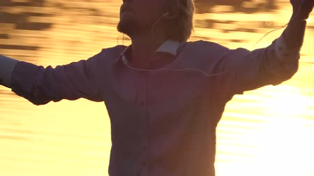 心のこもった : Jolly man listens to music on a lake bank at sunset in slo-mo
