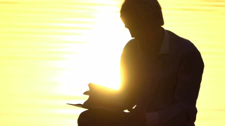tree stump : Blond man reads a book on a lake bank at a sunset Stock Footage