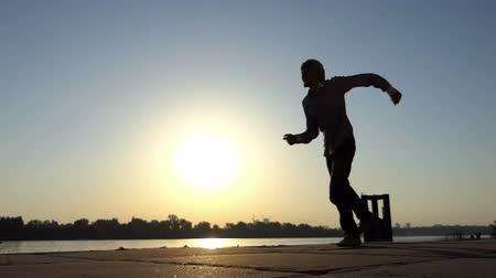 ucraniano : Optimistic man dances disco on a river bank in summer in slo-mo
