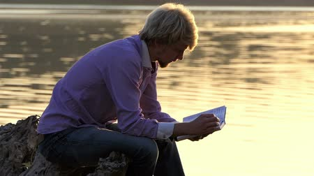 bible study : Student sits on a lake bank and reads a manual