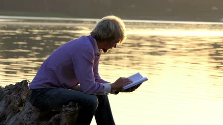 harcerz : Blond man reads a boot to write an article at a lake