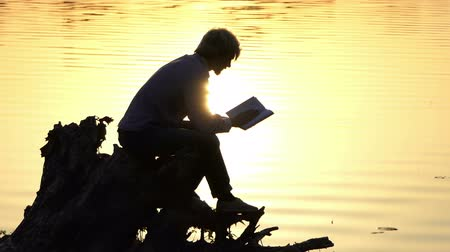 voluntário : Creative man reads a book to write an article at a lake