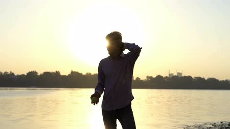 umutlu : Young man stands on a river bank at sunset in slo-mo