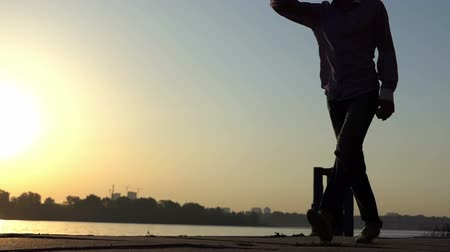umutlu : Happy man plays with a ball on a river bank at sunset in slo-mo