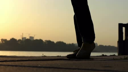 umutlu : Male feet walk on a river bank at a splendid sunset in slo-mo focusing.