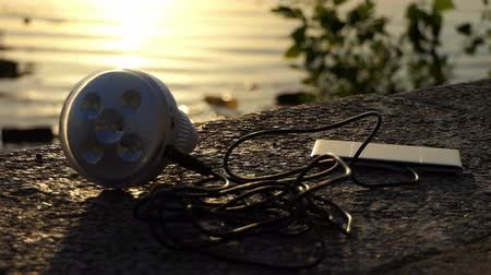 photovoltaic : Metallic microphone and a mobile lie on a riverbank Stock Footage