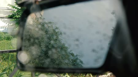 hátsó megvilágítású : The side window of the car is lowered with rain stones on it - slow motion. Stock mozgókép