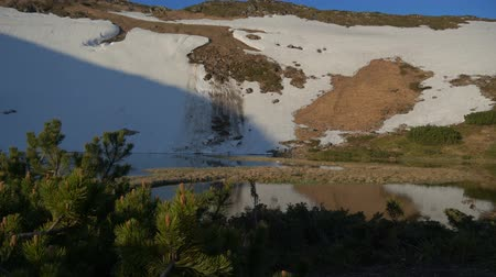 snow on grass : Steep slope with snow and a small lake at its foot in the Carpathians in slo-mo