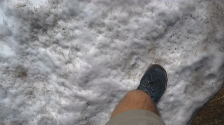 stepping : Male legs in sneakers climbing a snowy mountain in the Carpathians in slo-mo