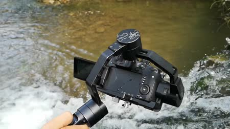 mirrorless : Mirrorless camera with electronical gimbal shooting waterfall in slow motion.