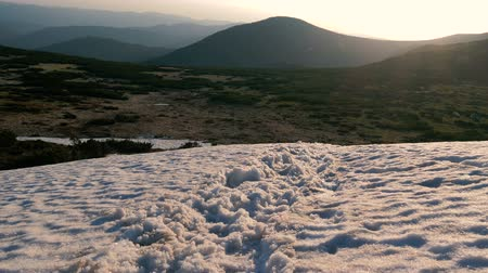 voetstappen : Mountain top covered with snowy drifts in the Carpathians in autumn in slo-mo