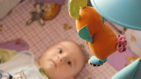 lion : Newborn baby lays on his bed and looking on the toys. Stock Footage