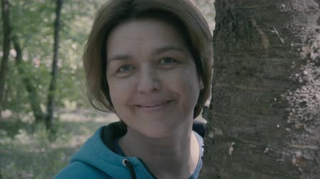 middle age : Middle age woman stands near tree and smile. Stock Footage