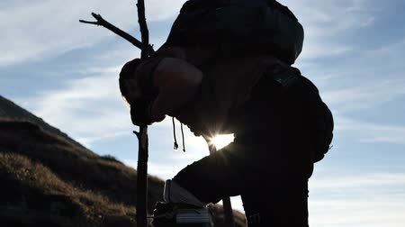 kule : 4k - man on the stilts climbs on the top of the mountain at sunset. Wideo